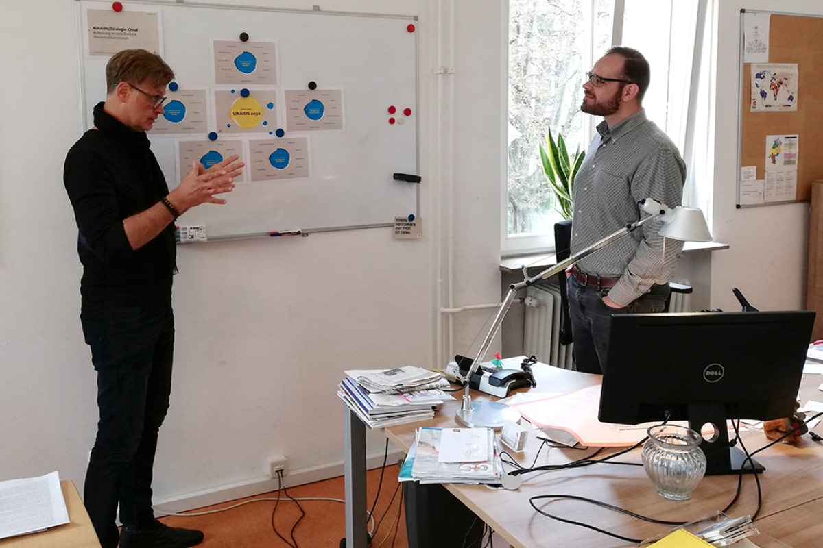 Zwei Personen stehen vor einem Whiteboard